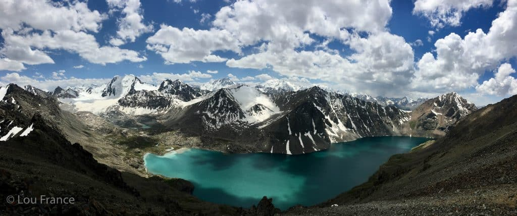 Beautiful aqua blue alpine lake with snow capped mountains. Ala Kul lake hike is popular backpackers in Kyrgyzstan